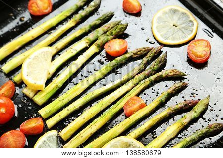 Fresh Baked Asparagus With Lemons And Tomatoes On Black Pan