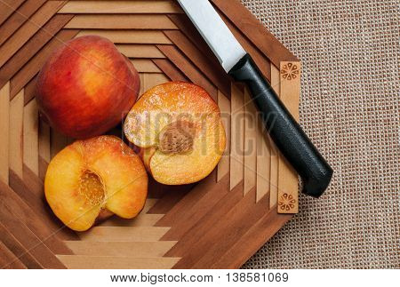 Ripe peaches fruit in basket on a brown background