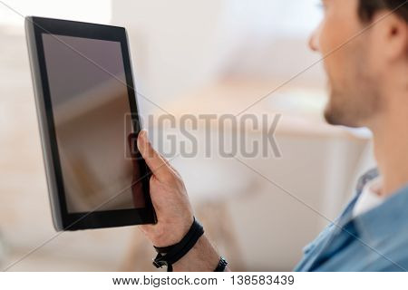 New technological advancements. Close up of tablet in hands of pleasant man holding it and using