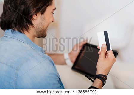 contemporary possibilities. Positive handsome smiling man holding credit card and using tablet while sitting on the couch