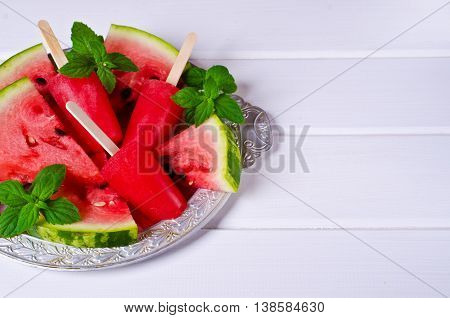 Homemade ice lolly of watermelon on a light wooden background. Selective focus.