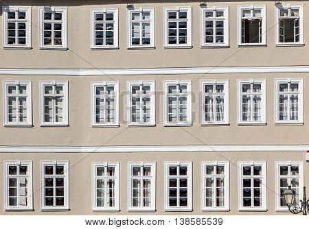 Facade Of Old House With Wooden Windows In Row