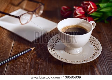 Coffee cup with note book and glases and flowers. Retro style pictures