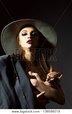 young sexy naked woman with bright makeup on pretty face and with body in round hat and coat holding purebreed pet cat of sphinx with no hair and wrinkled skin in studio on black background