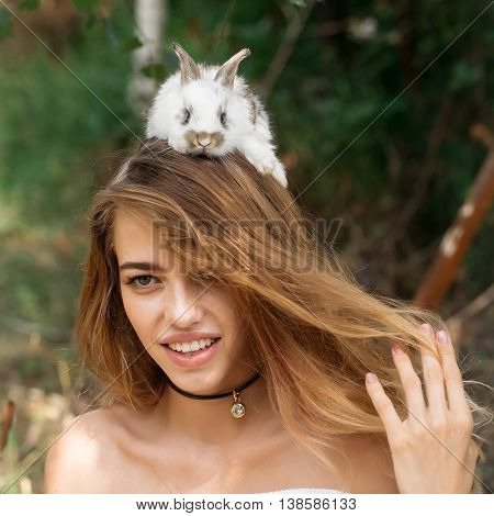Pretty young woman long-haired with cute little rabbit on head on summer day on natural background