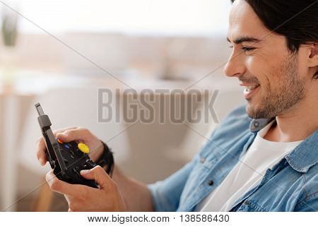 My childish hobby. Positive delighted smiling man holding game console and playing video games while resting at home