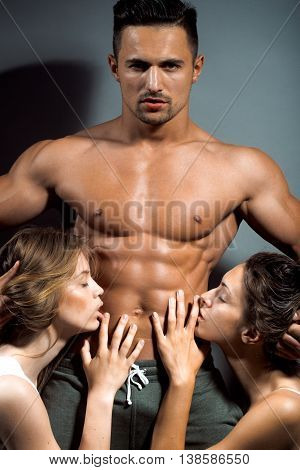 handsome young macho man with muscular sexy body and six packs on torso in pants and two naked pretty women in studio on grey background