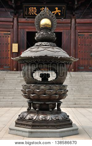 An incense burner in front of a the Grand hall (written in Chinese) at Baoshan Buddhist Temple in Baoshan district Shanghai China.
