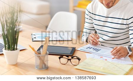 Do with pleasure. Positive delighted man sitting at the table and working with papers while being involved in work in the office