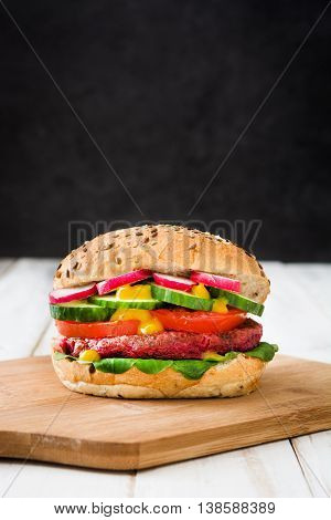 Veggie beet burger with lamb's lettuce, tomato, radish and cucumber on a white wooden table and black background