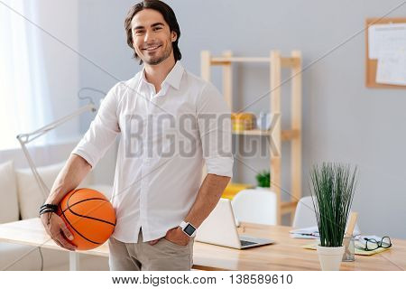 My hobby. Positive delighted handsome man holding basket ball and leaning on the table while standing in the office
