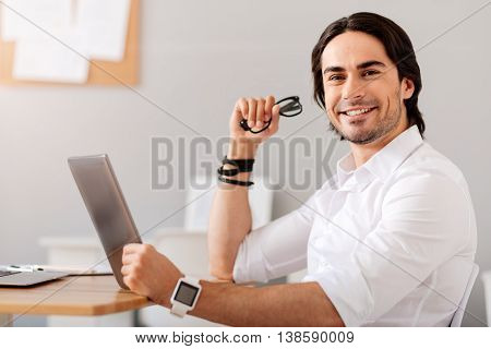 My favorite workplace. Cheerful smiling handsome man sitting at the table and being involved in work while using tablet