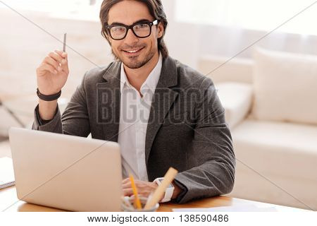 Like doing it. Cheerful handsome businessman sitting at the table and being involved in work while evincing joy
