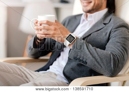 Feel yourself like at home. Positive smiling man sitting in the chair and resting while drinking coffee