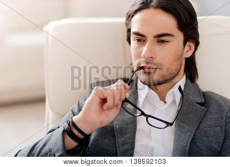 Mull it over. Concentrated handsome man sitting in the chair and holding his glasses while being involved in thoughts