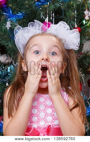 Portrait of the delighted little girl in front of a Christmas tree New Year
