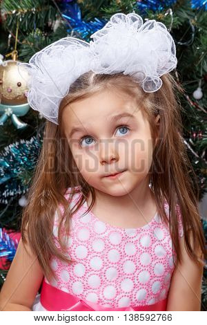 Portrait of the charming little girl in front of a Christmas tree New Year
