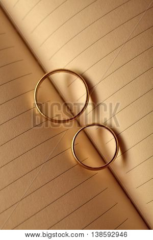 Wedding rings forming a heart onto a notebook