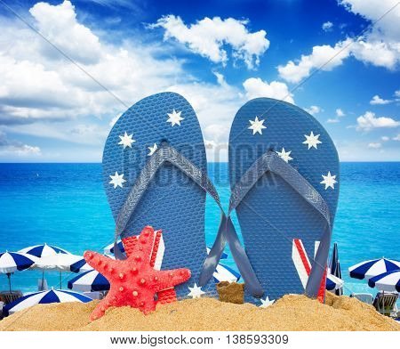 pair of blue sandals and starfish in sand by seaside