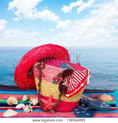 sunbathing accessories with straw hat isolated on towel by seaside