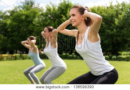 Follow healthy way of life. Cheerful smiling beautiful women expressing gladness while doing sport exercises