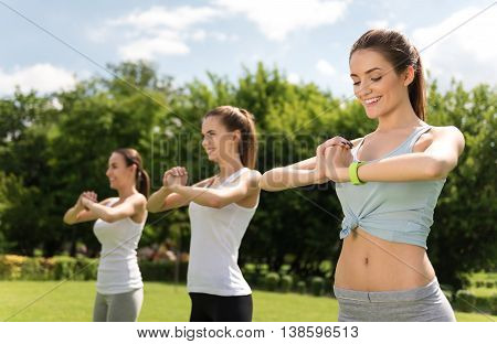 Rise your mood. Pleasant cheerful smiling women holding hands together and doing sport exercises while feeling happy outdoor
