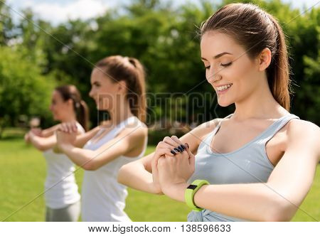 Refresh your mind. Cheerful delighted women holding hands together and smiling while doing sport activities outdoors