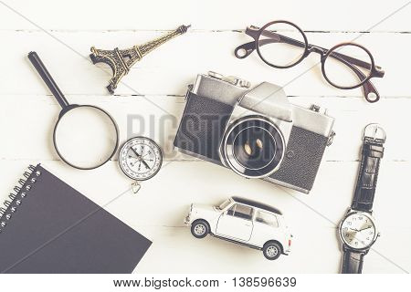 Travel accessories concept background with camera eyeglasses compass watch notebook magnifier toy model of eiffel and car on white wooden desk
