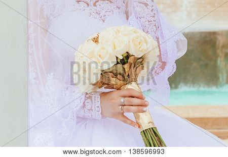 closeup hands of bridal couple with wedding rings on nature background