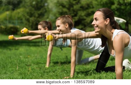 Work with enthusiasm. Cheerful beautiful smiling women holding dumbbells and doing sport activities with them while expressing joy