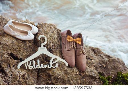 White hangers Wedding, the bow tie and groom's and bride's shoes on the rocks near ocean