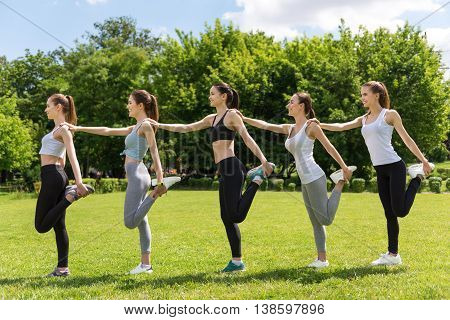 We are one team. Positive smiling women standing on one leg and holding each other while doing sport exercises