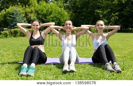 Right approach. Positive delighted smiling women lying on the roll mat and holding their hands behind the head while working their abs