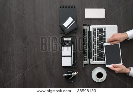 Corporate business manager working at office desk and using a digital touch screen tablet technology and communication concept