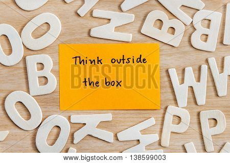 Handwriting letters words think outside the box on yellow sticky note with wood alphabet on wooden table Quote Think different concept Top view