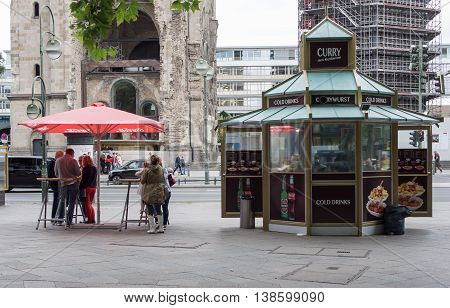 BERLIN GERMANY - JULY 15 2016: Tourists at Currywurst takeaway in front of famous Gedaechtniskirche in Kudamm Berlin