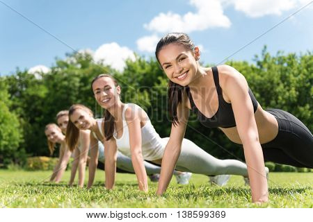 Sport enthusiasts. Cheerful sporty slim woman doing a press up and smiling while doing exercises outdoors