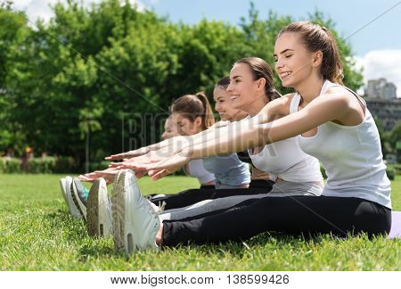 Touch the toes. Positive delighted attractive woman sitting on the grass and stretching while doing sport exercises