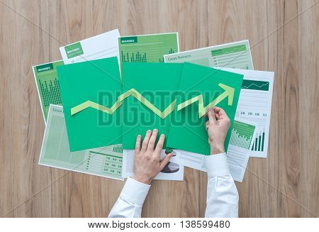 Businessman composing a successful financial chart with green arrow pointing up he is using paper cuts financial achievement and green business concept