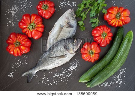 raw sea bream and fresh vegetables ingredients of the mediterranean cuisine and for a healthy diet. Flat lay photography.