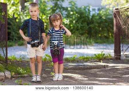 Little boy and a little girl wit two vintage camera standing together holding hands