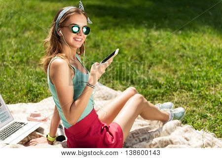 Favorite bits. Happy and cheerful young woman listening music using earphones and smart phone being in the park