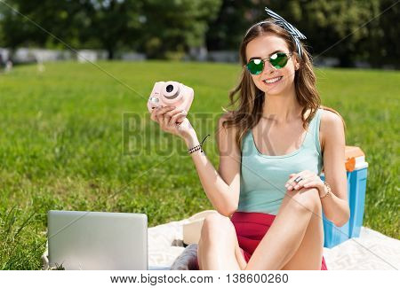 Lets make photos. Content and sincere young woman holding a camera while being in the park