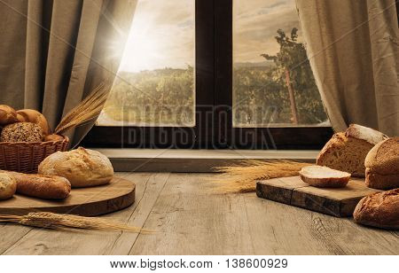 Freshly baked bread on a chopping board on the kitchen table in front of a window healthy eating concept