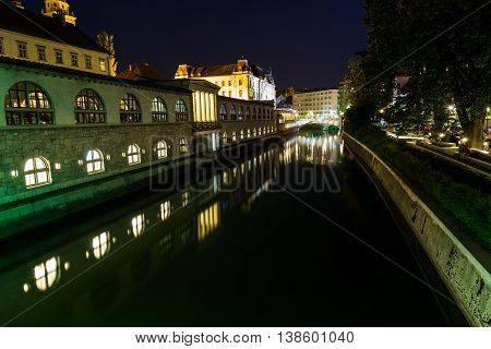LJUBLJANA SLOVENIA - 26TH MAY 2016: The outside of Ljubljana Central Market along the river at night. Reflections can be seen in the water