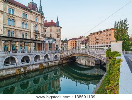 LJUBLJANA SLOVENIA - 27TH MAY 2016: A view along Ljubljana river in the morning towards the Triple Bridges. Reflections can be seen in the water