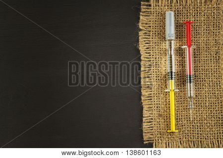 Old burlap on a black wooden board with syringes