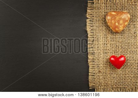 Old burlap on a black wooden board with heart
