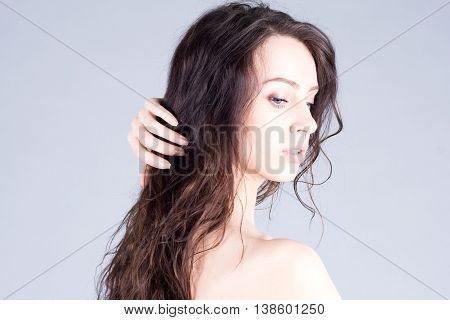 Pretty woman with wavy hair touching her hair and looking down. Beauty woman.