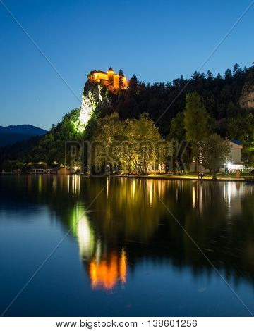 BLED SLOVENIA - 27TH MAY 2016: A view towards Bled Castle in Slovenia at night from across Bled Lake. People can be seen near the waterfront.